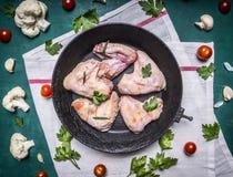 烹调的未加工的鸡翼成份排行了在老铸铁煎锅的圈子白色餐巾花椰菜蕃茄 图库摄影