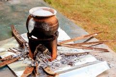 烹调的椰奶传统印地安人和Lankan泥罐在开火 免版税库存照片