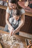 烹调的母亲帮助的女儿 库存照片