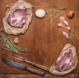烹调的猪肉牛排成份与肉和肉的刀子在土气木背景顶视图,框架分叉 免版税库存照片