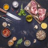 烹调的猪肉牛排调味料、油、刀子和叉子地方成份文本的,在木土气背景顶视图的框架 库存图片