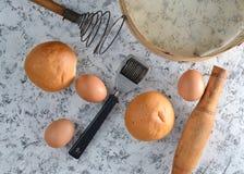 烹调的空间 厨房工具和成份烹调的在一张白色具体桌上 小圆面包,筛子,扫,滚针,鸡蛋 库存照片