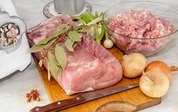 烹调的肉肉里脊肉通过一台绞肉机用葱和月桂叶 免版税库存图片