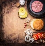 烹调的自创汉堡,蕃茄,洋葱圈,汉堡小圆面包边界,文本的地方成份在木土气背景上面 免版税图库摄影