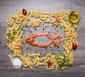 烹调的面团成份与熏制鲑鱼,被排行的框架,胡椒,盐,荷兰芹,三文鱼在鱼的形状被计划  免版税库存图片