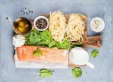 烹调的面团tagliatelle成份与三文鱼、菠菜和奶油 免版税库存照片