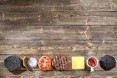 烹调的黑汉堡成份 烤肉小馅饼,小圆面包,葱,蕃茄,莴苣,腌汁,调味汁,乳酪  库存照片