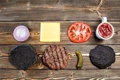 烹调的黑汉堡成份 烤肉小馅饼,小圆面包,葱,蕃茄,莴苣,腌汁,调味汁,乳酪  免版税库存图片