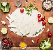 烹调的素食面卷饼成份以子弹密击,撒石灰,西红柿,香料,草本,与正文的大蒜乳酪在木头 库存图片