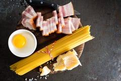 烹调的Carbonara面团、意粉有pancetta的,鸡蛋和干帕尔马干酪成份 alla茄子背景烹调新鲜的意大利norma荷兰芹意大利面食意粉蕃茄传统白色 面团 库存照片