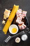 烹调的Carbonara面团、意粉有pancetta的,鸡蛋和干帕尔马干酪成份 alla茄子背景烹调新鲜的意大利norma荷兰芹意大利面食意粉蕃茄传统白色 面团 图库摄影