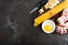烹调的Carbonara面团、意粉有pancetta的,鸡蛋和干帕尔马干酪成份 alla茄子背景烹调新鲜的意大利norma荷兰芹意大利面食意粉蕃茄传统白色 面团 免版税库存照片