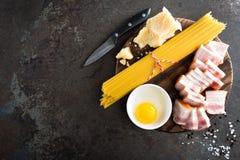 烹调的Carbonara面团、意粉有pancetta的,鸡蛋和干帕尔马干酪成份 alla茄子背景烹调新鲜的意大利norma荷兰芹意大利面食意粉蕃茄传统白色 面团 免版税库存图片