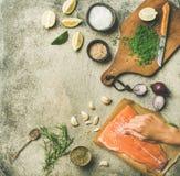 烹调盐味的三文鱼鱼片的女性手 免版税库存图片