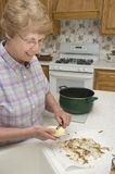烹调祖母她的厨房削皮土豆 免版税库存照片