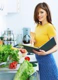 烹调站立在厨房里的妇女,用茅草盖从菜单的食谱 免版税库存图片