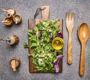 烹调素食沙拉用草本,黄油,盐,胡椒磨,一把木匙子和分叉在木土气背景的沙拉 免版税图库摄影