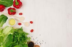 烹调绿色和红色菜新鲜的春天沙拉,在白色木背景,边界,顶视图的香料 库存图片