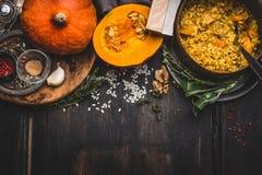 烹调罐素食南瓜意大利煨饭和匙子在黑暗的土气厨房用桌背景与烹调成份,顶视图, bo 免版税图库摄影