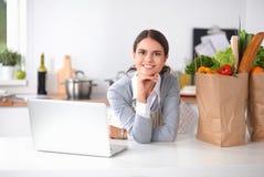 烹调美丽的少妇看有收据的膝上型计算机屏幕在厨房里 免版税库存照片