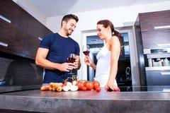烹调美好的年轻的夫妇,当喝在kitche时的酒 库存照片