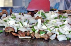 烹调肉和葱在平板炉 免版税库存图片