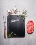 烹调背景用未加工的牛排、肉叉子、草本和香料,顶视图的黑板 库存图片