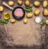 烹调自创汉堡包用油煎的土豆、新鲜的绞细牛肉在一个小煎锅草本,油和香料在木rusti 免版税库存图片