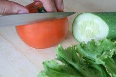 烹调菜沙拉的人的手在厨房里 库存照片