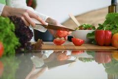 烹调菜沙拉的人的手特写镜头在玻璃桌上的厨房里与反射 免版税图库摄影