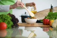 烹调菜沙拉的人的手特写镜头在玻璃桌上的厨房里与反射 图库摄影