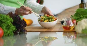 烹调菜沙拉的人的手特写镜头在玻璃桌上的厨房里与反射 库存图片