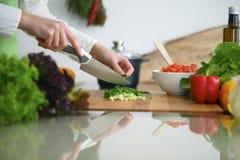 烹调菜沙拉的人的手特写镜头在玻璃桌上的厨房里与反射 免版税库存照片