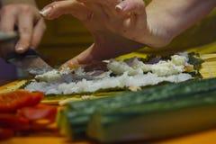 烹调菜沙拉的人的手特写镜头在厨房里 免版税库存照片
