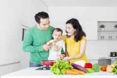 烹调菜的两个父母和女儿 图库摄影