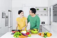 烹调菜的夫妇在厨房里 免版税图库摄影