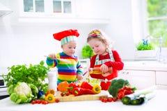 烹调菜的孩子在一个白色厨房里 免版税库存图片