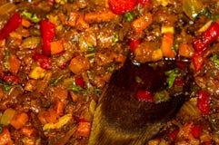 烹调葱、红萝卜、辣椒粉、蕃茄、草本和香料汤的一个烘烤在向日葵油在煎锅 免版税库存图片