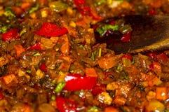 烹调葱、红萝卜、辣椒粉、蕃茄、草本和香料汤的一个烘烤在向日葵油在煎锅 图库摄影