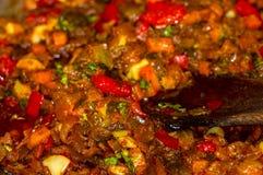 烹调葱、红萝卜、辣椒粉、蕃茄、草本和香料汤的一个烘烤在向日葵油在煎锅 免版税图库摄影