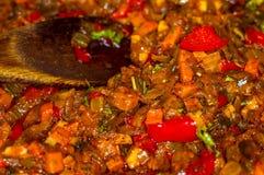 烹调葱、红萝卜、辣椒粉、蕃茄、草本和香料汤的一个烘烤在向日葵油在煎锅 库存图片