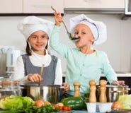 烹调蔬菜汤的两个小女孩 库存图片