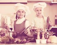 烹调蔬菜汤的两个小女孩 免版税库存照片