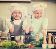 烹调蔬菜汤的两个小女孩 免版税库存图片