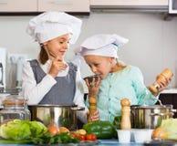 烹调蔬菜汤的两个小愉快的女孩 库存图片