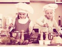烹调蔬菜汤的两个小愉快的女孩 免版税图库摄影