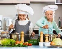 烹调蔬菜汤的两个小愉快的女孩 免版税库存照片