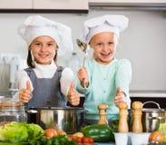 烹调蔬菜汤的两个快乐的女孩 库存图片