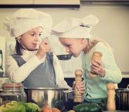 烹调蔬菜汤的两个快乐的女孩 库存照片