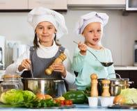 烹调蔬菜汤的两个快乐的愉快的女孩 库存图片